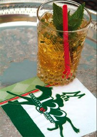 a glass of mint julep on a silver tray
