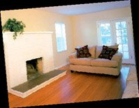 a nearly empty living room with a loveseat and wood floors.