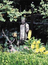 a statue stands behind an iron gate in a garden