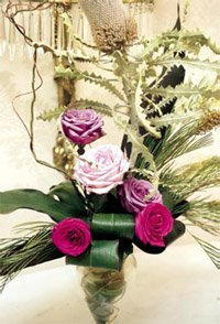 a flower arrangement with pink and red roses