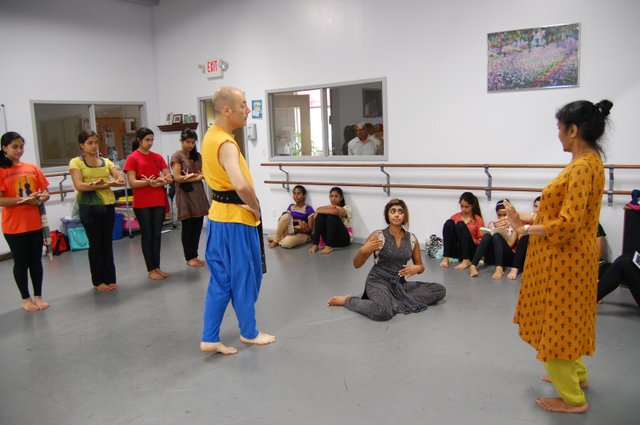 Matthew Traeger and Selena Swaminathan get instruction from Asha Prem.