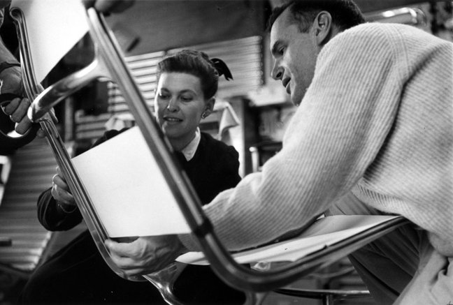 RAY AND CHARLES EAMES EXAMINING SLING LOCATIONS FOR FABRIC ON PROTOTYPE FOR THE ALUMINUM GROUP LOUNGE CHAIR