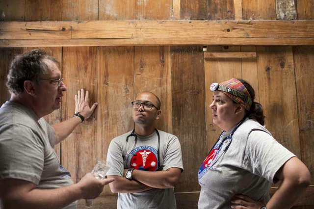 Volunteers Dr. Rick Bowen of St. Louis, Dr. Samip Shrestha of Kathmandu, and Dr. Dani Silvestre of São Paulo, Brazil, discuss a patient who they think may have appendicitis.