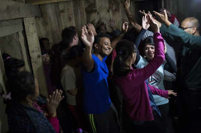 Prakash Shahi (left), a project coordinator for the medical mission and an electrical engineer who lives in St. Louis, and Dr. Shubha Argal of Kathmandu (second from left) dance with other volunteers and villagers during a welcome party in Tilche.