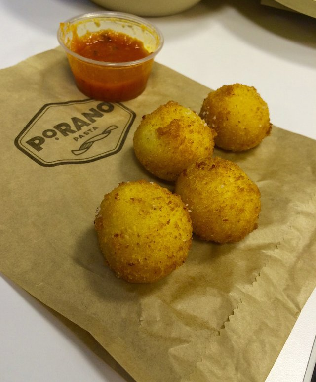 Risotto balls served casually in a parchment paper bag with a side of pomodoro..jpg